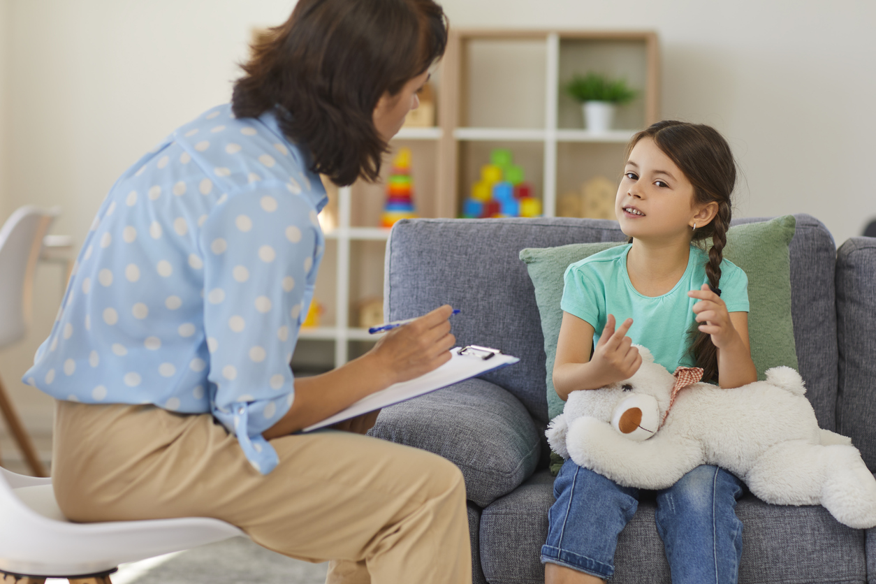 Supportive psychologist with clipboard listening to little child during therapy session. Preschool girl feeling at ease in therapist's office sharing her thoughts and concerns