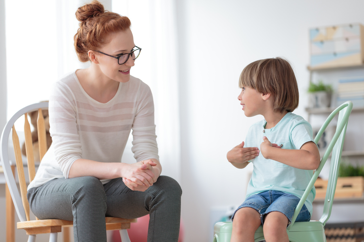 Smiling little boy sitting on chair talking with cheerful child psychotherapist during therapy session at office