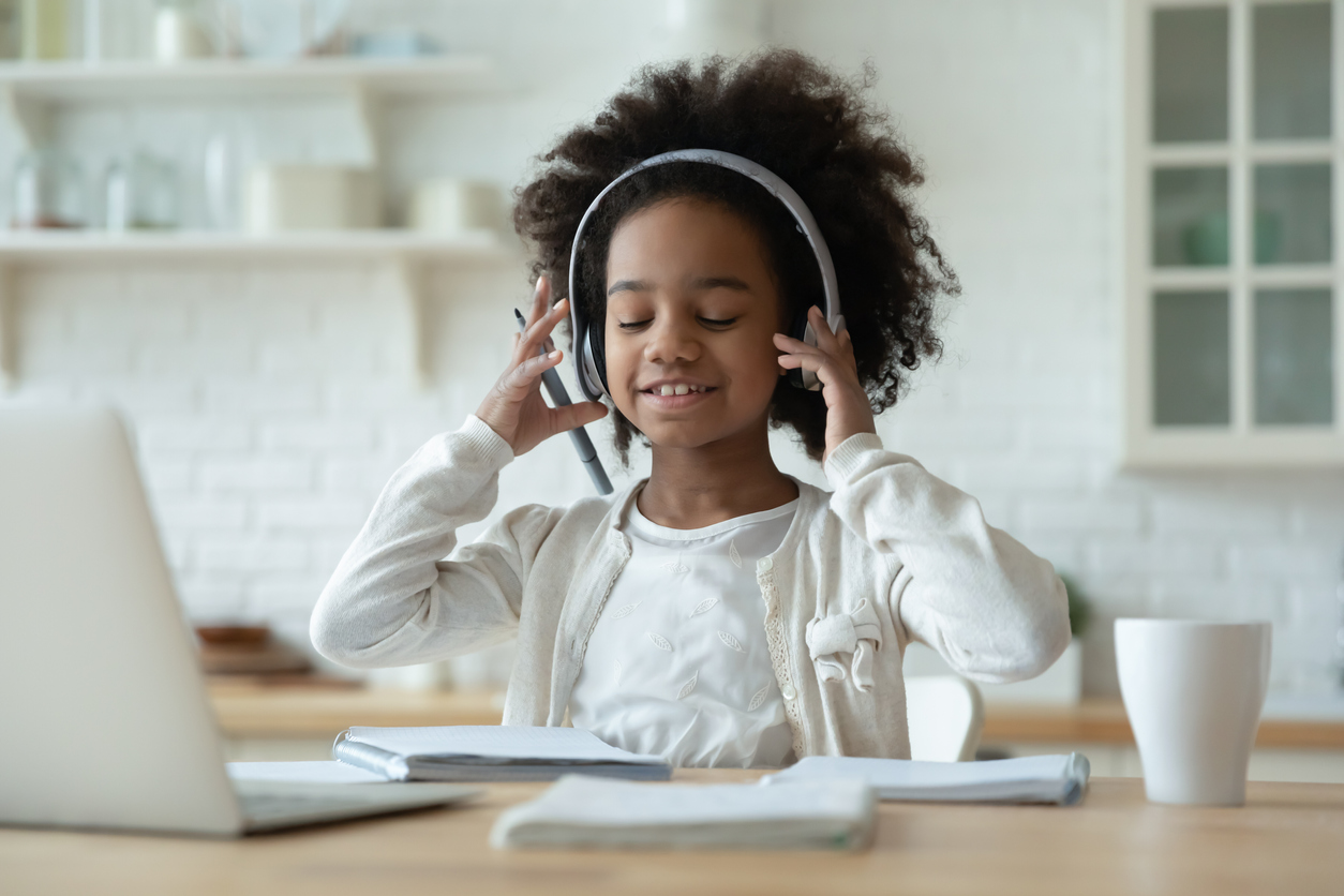 Little African girl sit at table learn school subject wears headphones use laptop listen audio lesson, enjoy study process. Self-education, new generation and modern tech usage making homework concept