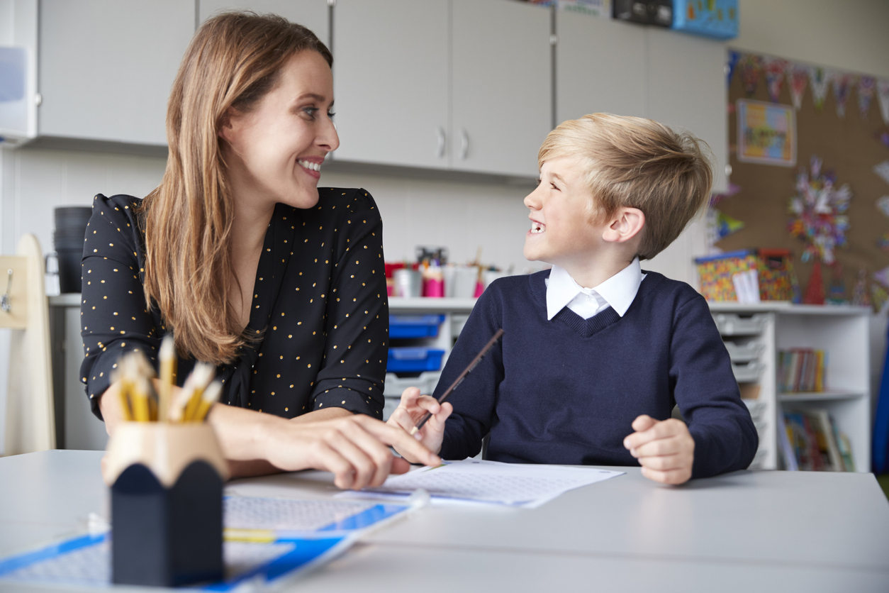 Young female primary school teacher and schoolboy sitting at a table working one on one, looking at each other smiling, front view, close up